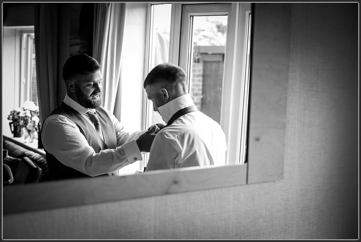 Best man helping the groom to get ready